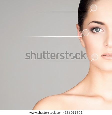 Close-up portrait of young, fresh and natural woman with the dotted arrows on her face - stock photo