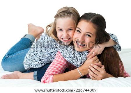 Close up portrait of young girl embracing older teen sister on bed.