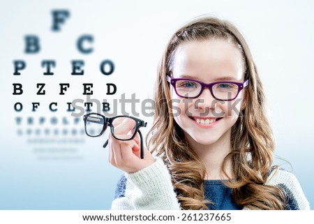Close up portrait of young girl holding glasses with test chart in background. - stock photo