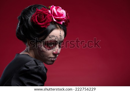 Close-up portrait of young girl in black dress with Calaveras makeup and a red flower in her black hair looking aside isolated on red background with copy place - stock photo