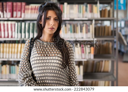 Close up portrait of young girl looking at camera in college library. - stock photo