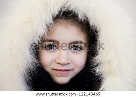 Close-up portrait of young girl wearing fur hood and smiling - stock photo