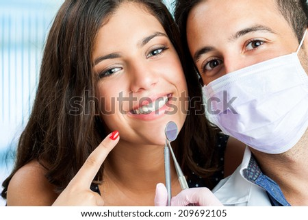 Close up portrait of Young girl with dentist pointing at mouth. - stock photo