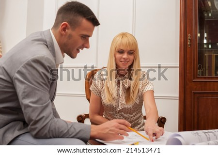 Close-up portrait of young handsome architect discussing ground plan with client sitting at the table in design studio,  pointing at architectural plan with pencil, creative discussion concept - stock photo