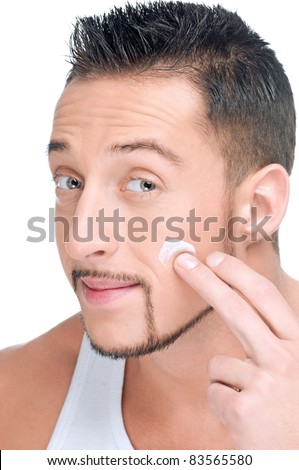 Close up portrait of young handsome man applying male cosmetic creme on face - stock photo
