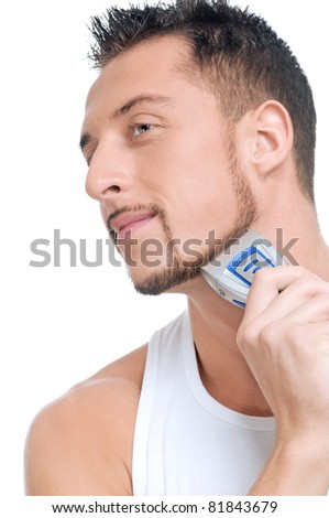 Close up portrait of young handsome man with perfect skin and hair. Shaving by electric shaver - stock photo
