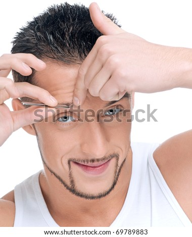 Close up portrait of young handsome man with perfect skin and hair. Tweezers eyebrow - stock photo