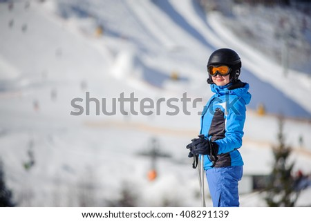 Close-up portrait of young happy female skier against ski slopes on background. Woman is wearing helmet skiing glasses gloves and blue ski suit. Winter sports concept. Bukovel - stock photo