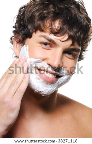 Close-up portrait of young happy man's face with shaving cream