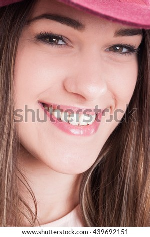 Close-up portrait of young happy smiling woman with perfect white teeth wearing hat and looking charming - stock photo