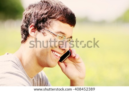 Close up portrait of young hispanic man wearing glasses and t-shirt, sitting in spring park outdoors, holding mobile phone near his head and laughing - communication concept - stock photo