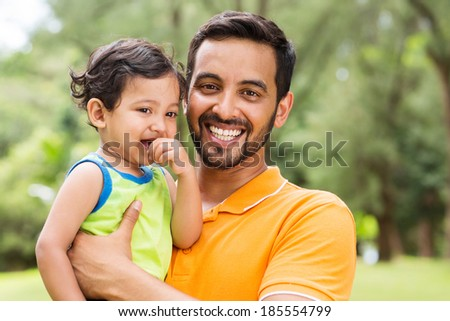 close up portrait of young indian father and baby boy outdoors - stock photo