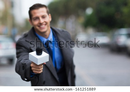 close up portrait of young journalist giving microphone - stock photo