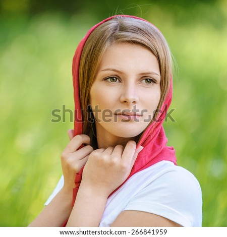 Close-up portrait of young joyous beautiful blonde woman wearing red headscarf and looking somewhere at summer green park. - stock photo