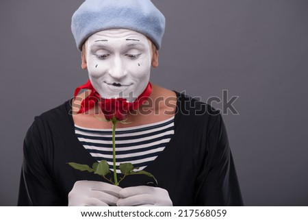 Close-up portrait of young male mime with white face and grey hat holding a red rose and gently looking at this flower isolated on grey background with copy place - stock photo