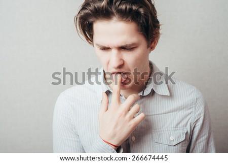 Close Up portrait of young man, annoyed, frustrated fed up sticking fingers in ??? throat. - stock photo