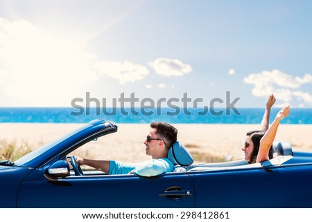 Close up portrait of young man driving blue convertible. Girlfriend sitting in back raising arms in air. - stock photo