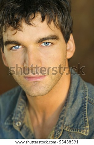 Close-up portrait of young man in denim shirt against brown background - stock photo