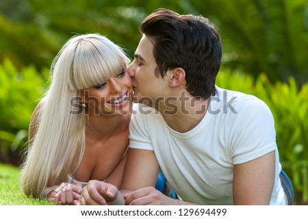 Close up portrait of young man kissing his girlfriend on cheek outdoors. - stock photo