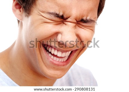 Close-up portrait of young man laughing out loud - stock photo
