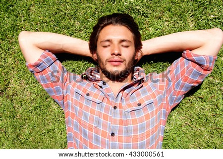 Close up portrait of young man lying in the grass relaxing - stock photo