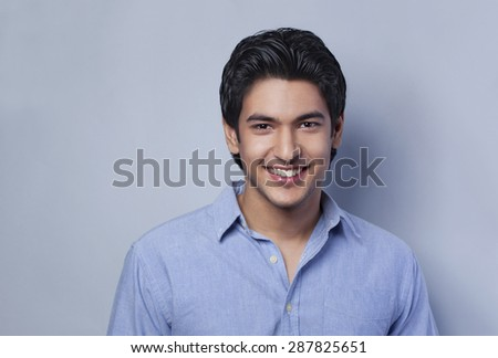 Close-up portrait of young man smiling - stock photo