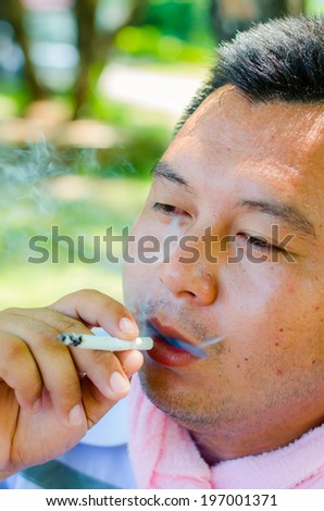 Close up portrait of young man smoking cigarette - stock photo