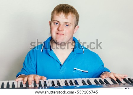 Close up portrait of young man with down syndrome playing the piano.Studio shot of pianist with hands on keyboard.