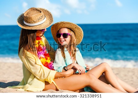 Close up portrait of young mother and daughter on summer holidays. Two young women in swimwear with straw hats and fun purple sunglasses. - stock photo