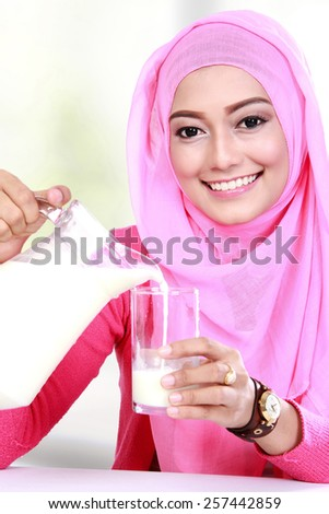close up portrait of young muslim woman pouring milk into a glass - stock photo