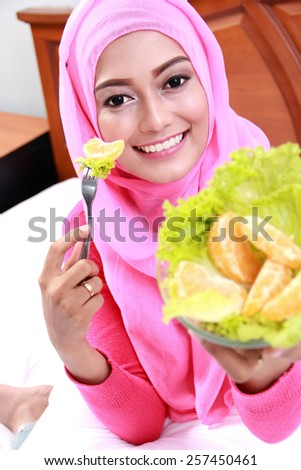 close up portrait of young muslim woman showing fruit and vegetable for her breakfast on bed - stock photo