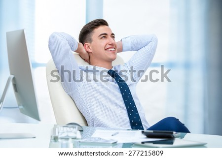 Close up portrait of young office worker daydreaming at desk. Young man sitting at desk with hands behind head and looking up. - stock photo