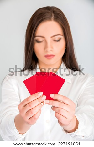Close-up portrait of young pretty business woman holding red credit card.  focus on the credit card - stock photo