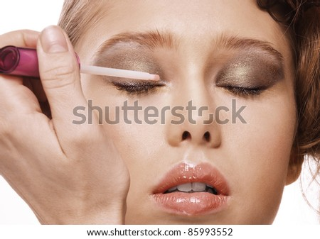 Close-up portrait of young pretty woman being made-up with brush against white background. - stock photo
