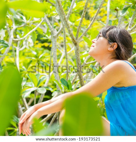 Close-up Portrait of young pretty woman with the blue dress and sunglasses sitting of the green national park  and looking at  side - stock photo