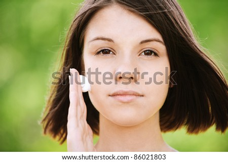 Close-up portrait of young serious beautiful brunette woman putting white cream on her face. - stock photo