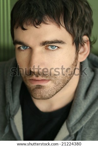Close-up portrait of young serious man - stock photo