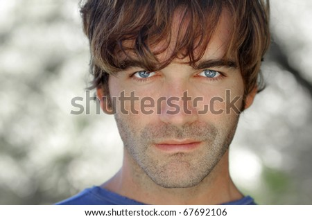 Close-up portrait of young serious man outdoors