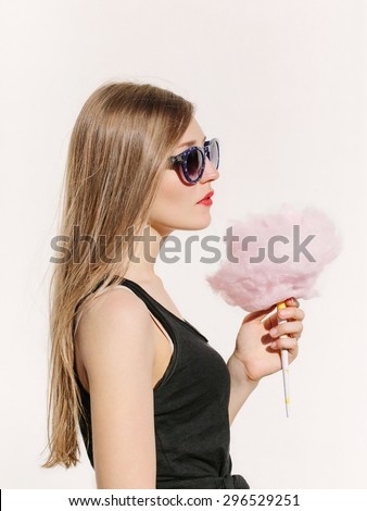 Close up portrait of young sexy woman with pink cotton candy. Lifestyle portrait. White background, not isolated - stock photo