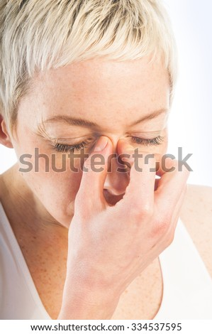 Close up portrait of young sick woman having flu or sinus infection  isolated on white background. Health care concept. Studio shot. - stock photo