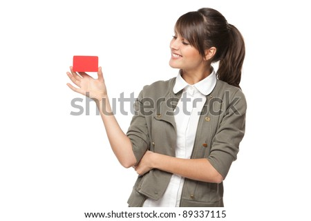 Close-up portrait of young smiling business woman holding credit card and and looking at it isolated on white background