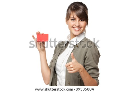 Close-up portrait of young smiling business woman holding credit card and showing thumb up sign isolated on white background - stock photo