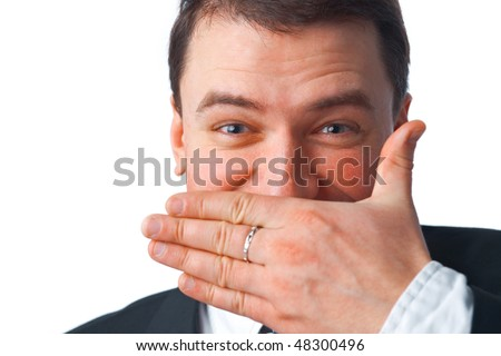 Close up portrait of young smiling businessman covering mouth with his hand while looking at you over white