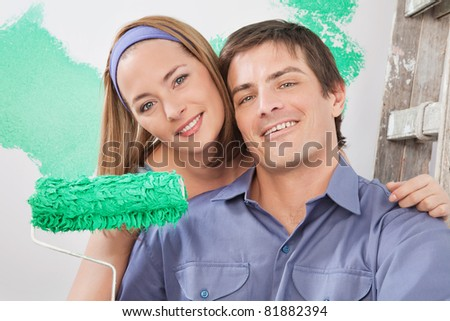Close-up portrait of young smiling couple with paint roller - stock photo
