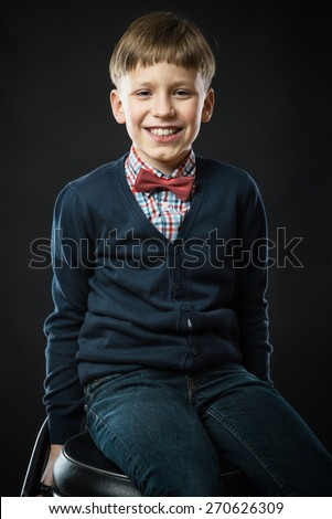 Close up portrait of young smiling cute boy in bow tie - stock photo
