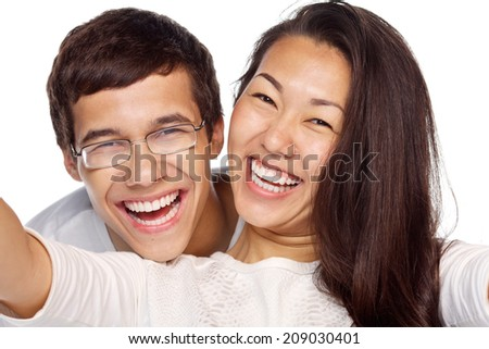 Close-up portrait of young smiling interracial couple taking selfie isolated on white background - stock photo