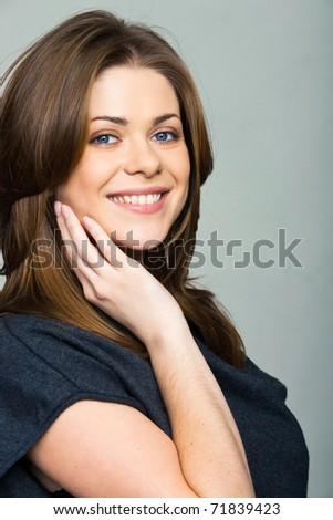 Close-up portrait of young smiling woman standing over white background - stock photo