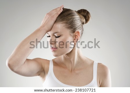Close-up portrait of young stressed woman touching her forehead in pain. Memory loss and headache concept. - stock photo