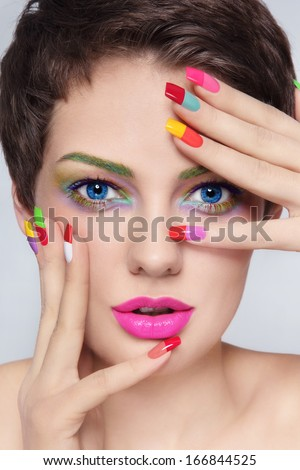 Close-up portrait of young stylish beautiful girl with fancy make-up and colorful french manicure - stock photo
