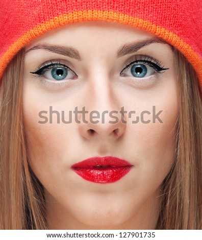 Close-up portrait of young stylish beautiful woman with blue eyes, red lips and red hat - stock photo